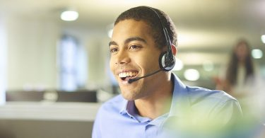 a young male call centre worker takes a call.