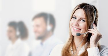 Happy and smiling woman with microphone during telemarketing job