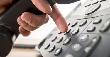 Closeup of dialing a telephone number on a black landline telephone. Conceptual of global communication, business support and customer care.