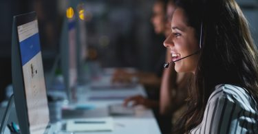 Cropped shot of an attractive young female call center agent working late in the office with her colleagues in the background