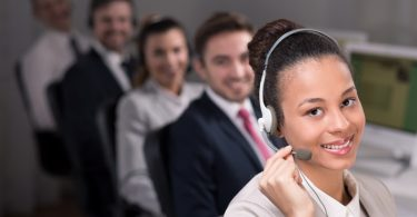 Telemarketer woman with headphones and microphone, smiling